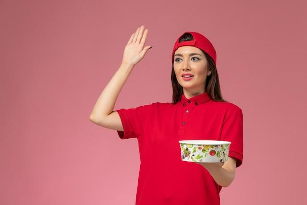 Weiblicher kurier der vorderansicht in rotem uniformumhang mit lieferschüssel auf ihren händen, die auf hellrosa wand winken, dienstlieferungsmitarbeiter Kostenlose Fotos