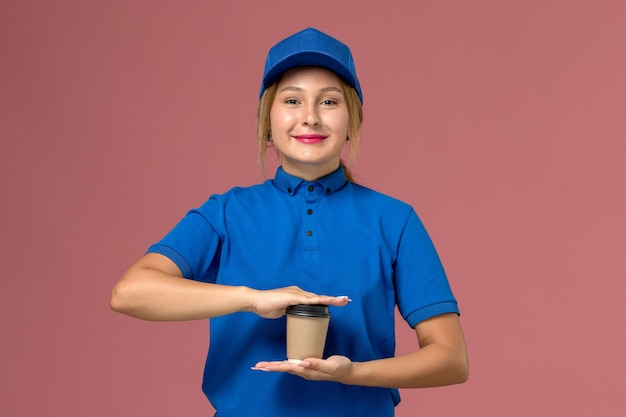 Weiblicher kurier in der blauen uniform, die die tasse kaffee mit leichtem lächeln auf rosa, dienstuniform-lieferjobarbeiter hält Kostenlose Fotos