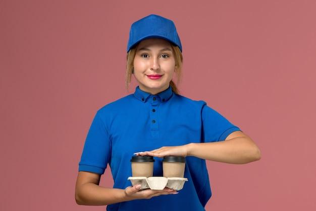 Weiblicher kurier in der blauen uniform, die lieferbecher des kaffees lächelnd auf rosa, dienstuniform-lieferauftrag hält Kostenlose Fotos