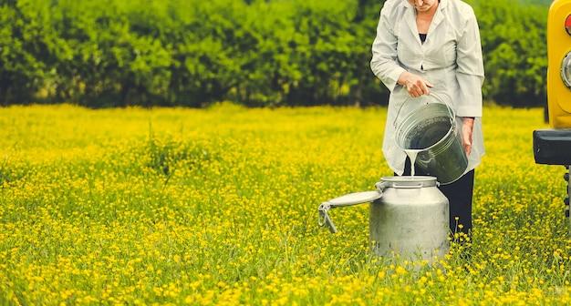 Weiblicher landarbeiter, der milch in einen metallischen behälter in der bauernhofzone hinzufügt Kostenlose Fotos