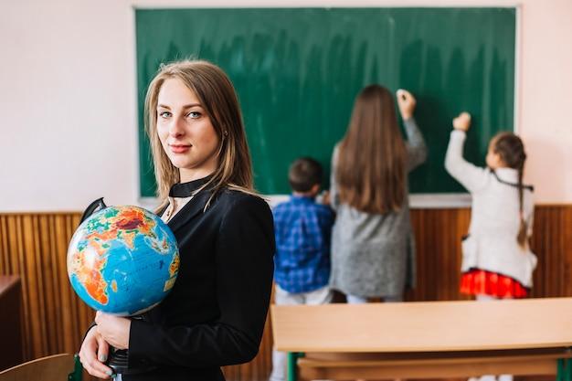 Weiblicher lehrer mit kugel auf klassenzimmerhintergrund Kostenlose Fotos