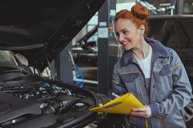 Weiblicher mechaniker, der an der autotankstelle arbeitet Premium Fotos