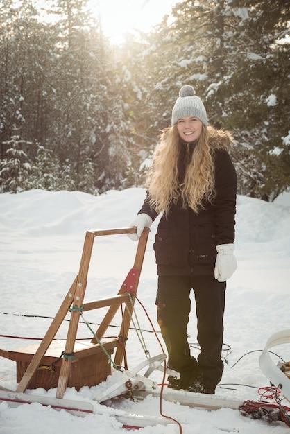 Weiblicher musher, der neben schlitten steht Kostenlose Fotos