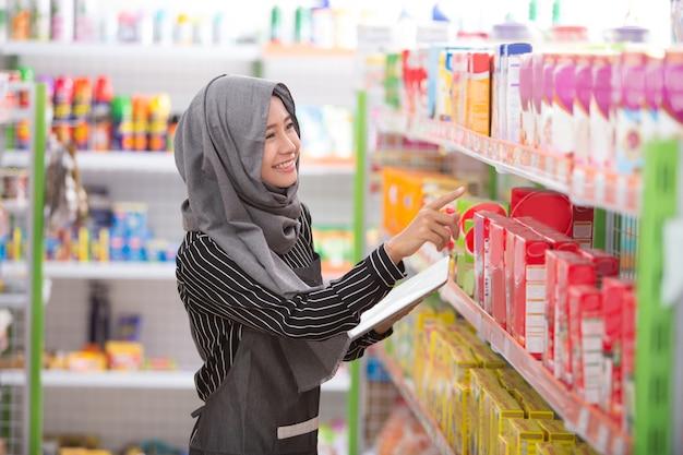 Weiblicher muslimischer ladenbesitzer, der am supermarkt arbeitet Premium Fotos