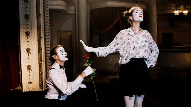 Weiblicher pantomime, der dem männlichen pantomimekünstler zeigt, der rote rose hält, stoppen sie geste Kostenlose Fotos