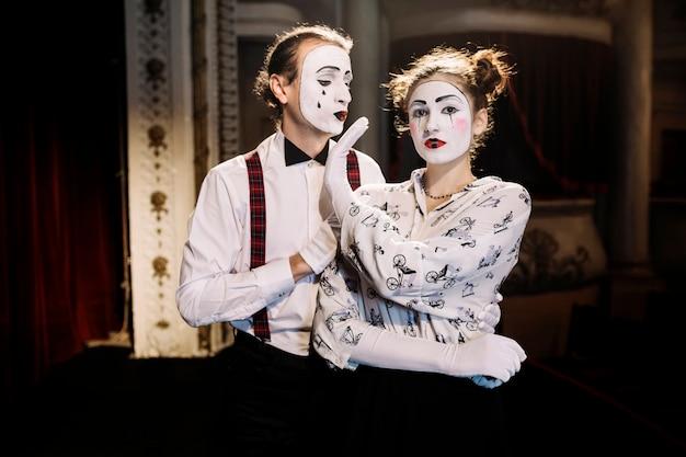 Weiblicher pantomime, der dem männlichen pantomimen kein handzeichen zeigt Kostenlose Fotos