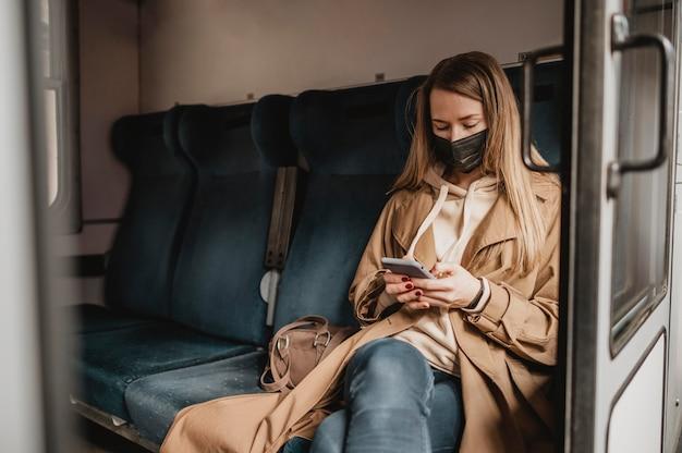 Weiblicher passagier, der in einem zug sitzt und medizinische maske trägt Kostenlose Fotos