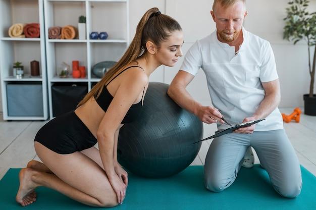Weiblicher patient mit männlichem physiotherapeuten, der zwischenablage betrachtet Kostenlose Fotos