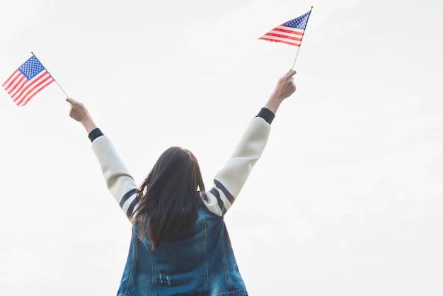 Weiblicher patriot mit flaggen in ausgestreckten händen Kostenlose Fotos