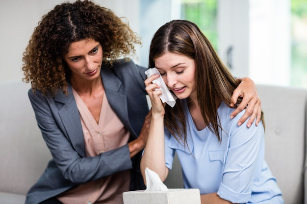 Weiblicher psychologe, der zu hause deprimierte frau auf sofa tröstet Premium Fotos