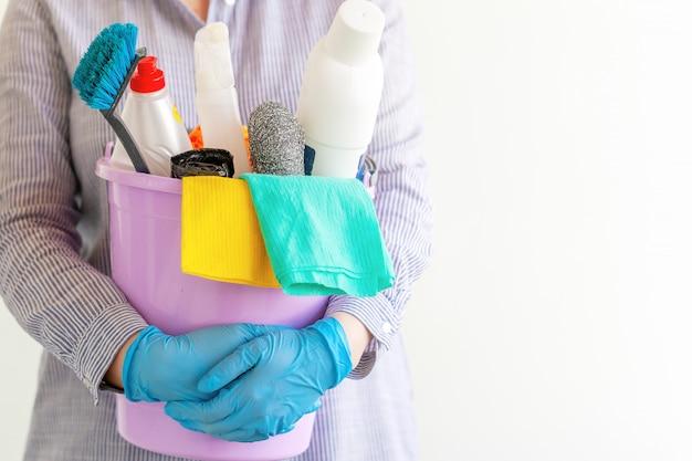 Weiblicher reiniger, der einen eimer mit putzzeug hält. Premium Fotos
