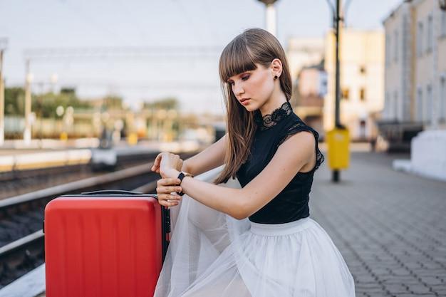 Weiblicher reisender mit rotem koffer, der zug am bahnhof wartet Premium Fotos