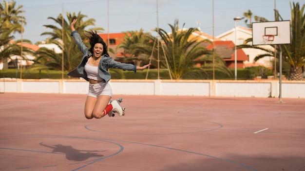 Weiblicher schlittschuhläufer, der über das fußballgericht springt Kostenlose Fotos