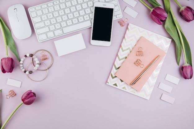 Weiblicher schreibtischarbeitsplatz mit tulpen, tastatur, gläsern, tagebuch und goldenen klipps auf veilchen Premium Fotos