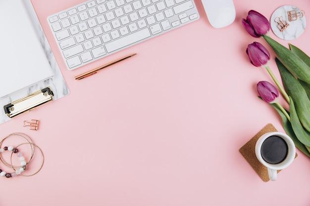 Weiblicher schreibtischarbeitsplatz mit tulpen, tastatur, goldene klipps auf rosa Premium Fotos
