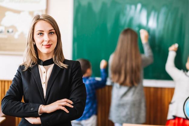 Weiblicher schullehrer auf hintergrund der tafel und der studenten Kostenlose Fotos