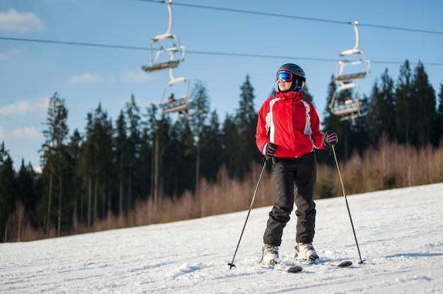 Weiblicher skifahrer, der mit skis auf schneebedeckter steigung am sonnigen tag steht Premium Fotos