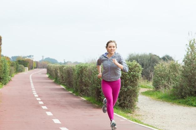 Weiblicher sprinter, der schnell auf stadionsbahn läuft Kostenlose Fotos