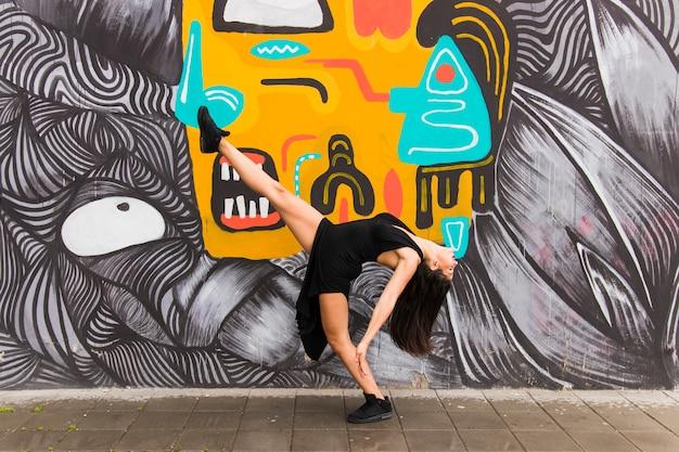 Weiblicher tänzer des tangos, der gegen kreative graffitiwand aufwirft Kostenlose Fotos