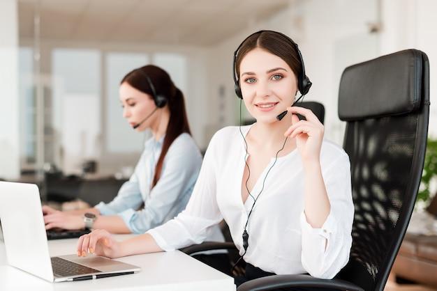 Weiblicher technischer kundendienstmitarbeiter mit dem kopfhörer, der geschäftsanrufe im firmenbüro beantwortet Premium Fotos