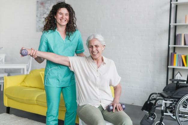Weiblicher therapeut, der lächelnde ältere frau mit dummköpfen unterstützt Kostenlose Fotos