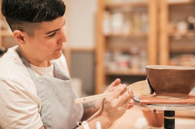 Weiblicher töpfer, der die handgemachte schüssel mit malerpinsel in der werkstatt malt Kostenlose Fotos