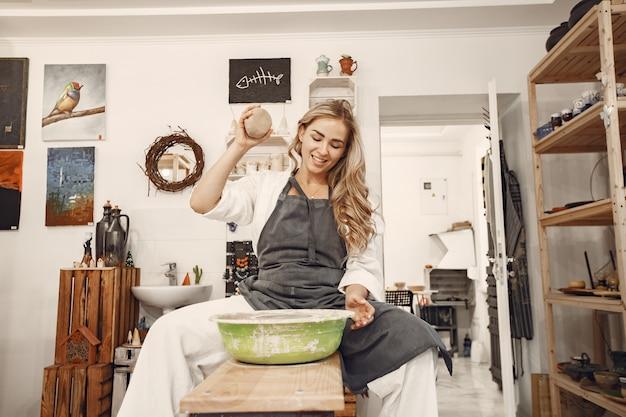 Weiblicher töpfer, der mit ton auf rad im studio arbeitet. ton mit wasser spritzte um die töpferscheibe. Kostenlose Fotos