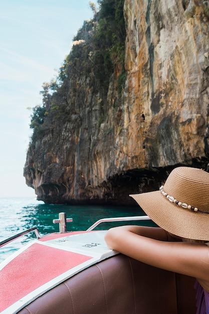 Weiblicher tourist, der auf bootsreise nahe der klippe sich lehnt Kostenlose Fotos