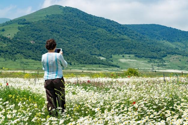 Weiblicher tourist, der fotos mit digitalem tablett macht, das im schönen feld voller blühender blumen vor den bergen in armenien steht Premium Fotos