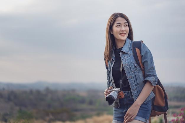 Weiblicher tourist mit rucksack und kamera in der landschaft Premium Fotos