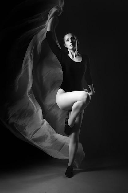 Weiblicher turner, der auf schwarzem aufwirft Premium Fotos