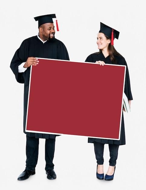 Weiblicher und männlicher absolvent, der einen kopienraum hält Kostenlose Fotos