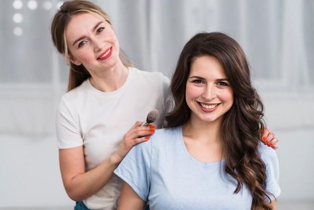 Weiblicher visagiste mit dem kunden, der an der kamera lächelt Kostenlose Fotos