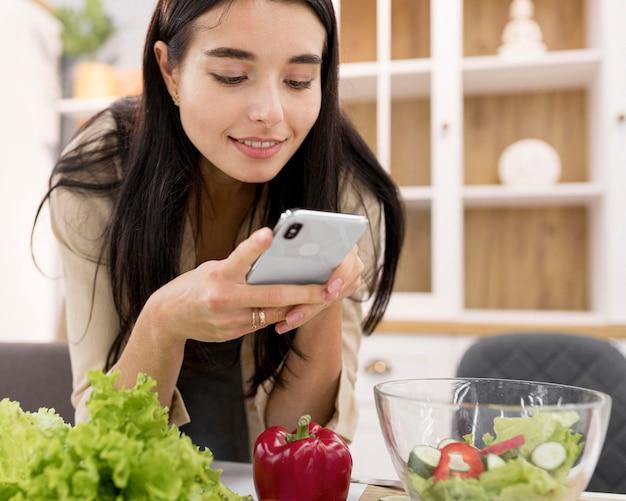 Weiblicher vlogger, der bilder zu hause mit smartphone nimmt Kostenlose Fotos