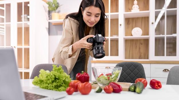 Weiblicher vlogger zu hause, der bilder mit kamera macht Kostenlose Fotos