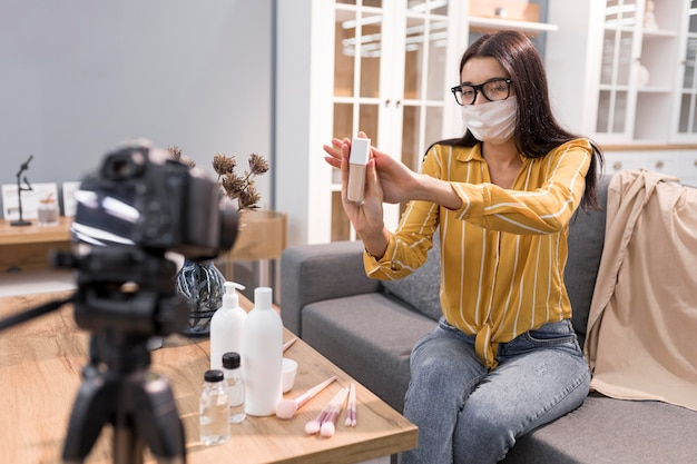 Weiblicher vlogger zu hause mit kamera und gesichtsmaske Kostenlose Fotos