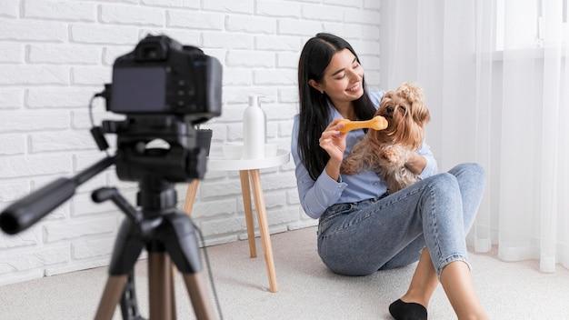 Weiblicher vlogger zu hause mit kamera und hund Kostenlose Fotos