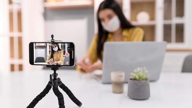 Weiblicher vlogger zu hause mit laptop und smartphone Kostenlose Fotos