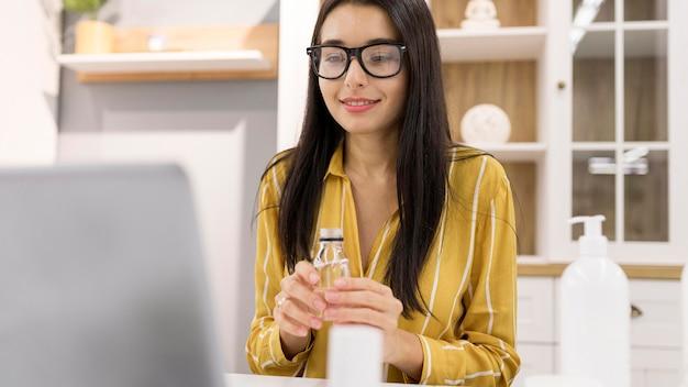 Weiblicher vlogger zu hause mit produkt und laptop Kostenlose Fotos
