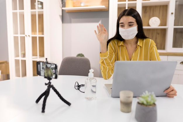 Weiblicher vlogger zu hause mit smartphone und medizinischer maske Kostenlose Fotos