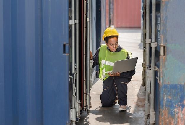 Weiblicher vorarbeiter, der die nummer an der behälterkastentür mit einem laptop überprüft Premium Fotos