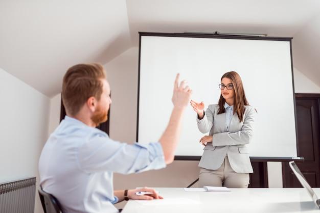 Weiblicher vorführer, der frage stellt und ein mann, der hand anhebt, um zu antworten. Premium Fotos