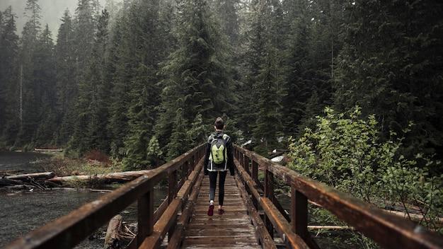 Weiblicher wanderer, der auf die holzbrücke führt in richtung zum wald geht Kostenlose Fotos