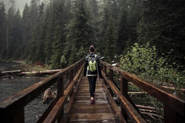 Weiblicher wanderer, der auf holzbrücke geht Kostenlose Fotos