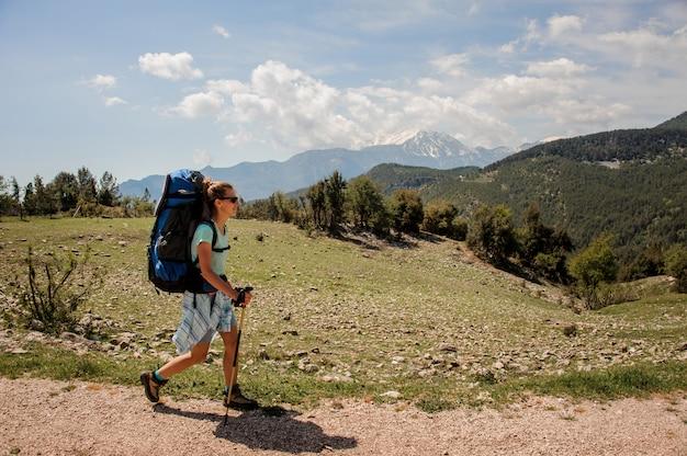 Weiblicher wanderer, der herauf die straße in den hügeln reist Premium Fotos