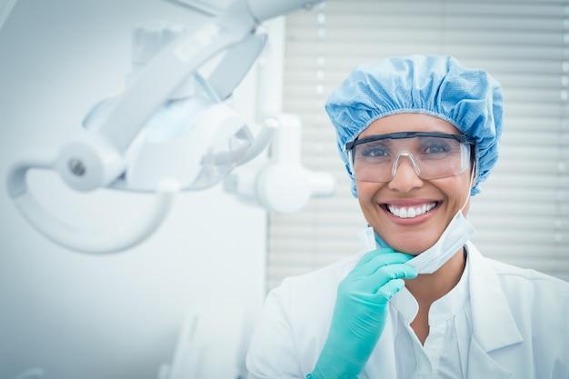 Weiblicher zahnarzt, der chirurgische kappe und sicherheitsgläser trägt Premium Fotos
