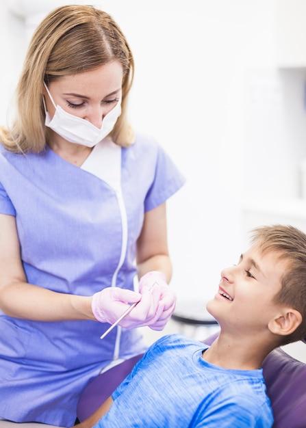 Weiblicher zahnarzt, der die zähne des glücklichen jungen in der klinik überprüft Kostenlose Fotos