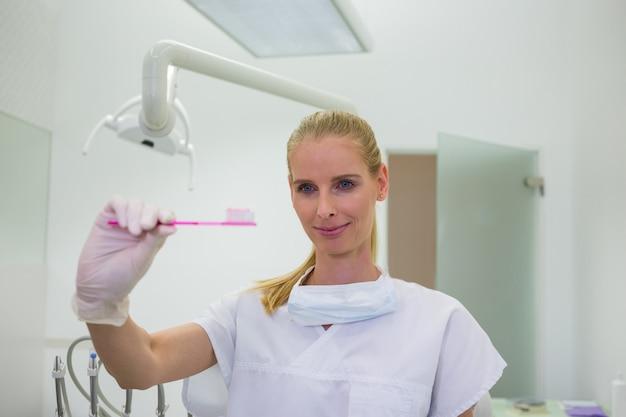 Weiblicher zahnarzt, der eine zahnbürste hält Kostenlose Fotos
