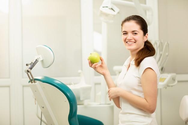 Weiblicher zahnarzt, der einen grünen apfel, ein zahnpflege- und ein verhinderungskonzept lächelt und hält Premium Fotos