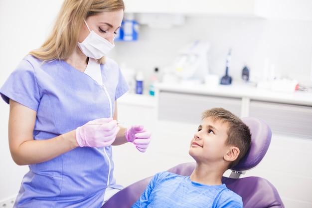 Weiblicher zahnarzt mit der chirurgischen maske, die naher patienten des scalers in der klinik hält Kostenlose Fotos